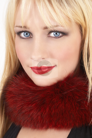 Portrait of beautiful blonde woman stock photo, Portrait of a beautiful blonde woman with light blue eyes and bright make-up wearing red fur around her neck on white background by Elena Weber (nee Talberg)
