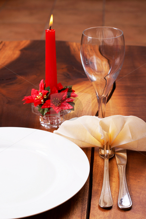 Beautiful table setting with a candle in the background stock photo, Beautiful table setting with a candle in the background by Elena Weber (nee Talberg)