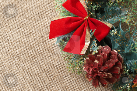 Christmas decoration stock photo, Christmas decoration with bow, leaves and cone on material background with copy space by Elena Weber (nee Talberg)
