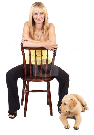 Portrait of beautiful blonde woman with dog stock photo, Portrait of a beautiful blonde woman with light blue eyes and colorful make-up sitting on a chair with golden retriever puppy next to her by Elena Weber (nee Talberg)
