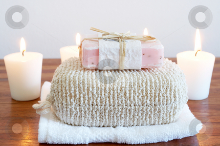 Relaxing spa scene with body products stock photo, Relaxing spa scene with sponge, handmade soap, white towel and candles in the background by Elena Weber (nee Talberg)