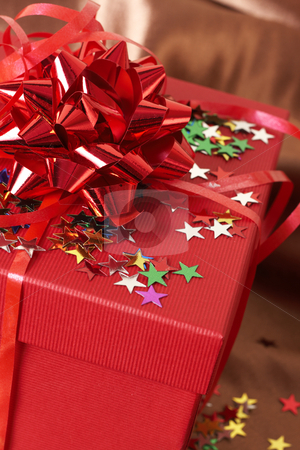 Red gift box with bows and stars stock photo, Red gift box with bows and stars on golden silk background by Elena Weber (nee Talberg)