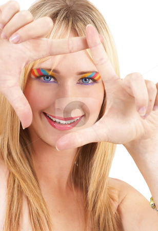 Portrait of beautiful blonde woman stock photo, Portrait of a beautiful blonde woman with light blue eyes and colorful make-up forming a frame with her hands isolated on white background by Elena Weber (nee Talberg)