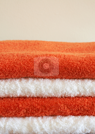 Stack of color towels stock photo, Stack of white and orange fluffy towels on light background by Elena Weber (nee Talberg)