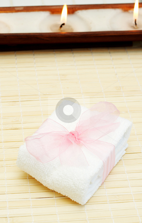 Relaxing spa scene with body products stock photo, Relaxing spa scene with small white towel with pink organza ribbon around it and candles in the background by Elena Weber (nee Talberg)
