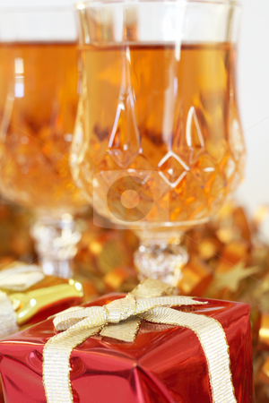 Colorful Christmas gift with sherry stock photo, Colorful Christmas gift box with ribbons and golden tinsel and two glasses of sherry on white background. Shallow depth of field by Elena Weber (nee Talberg)