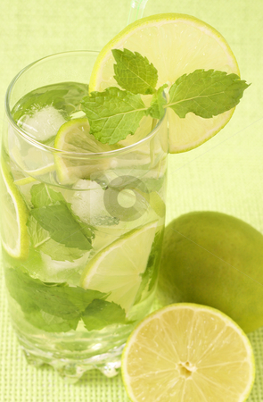 Mojito cocktail on green background stock photo, Mojito cocktail with lime, mint leaves and ice on green background by Elena Weber (nee Talberg)