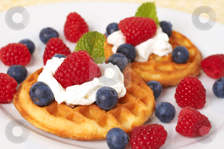 Belgian waffles with berries and cream stock photo, Belgian waffles with fresh raspberries, blueberries, mint leaves and cream on white plate by Elena Weber (nee Talberg)