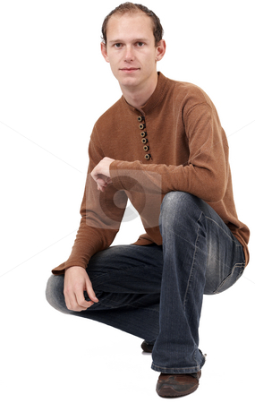 Young caucasian man sitting down stock photo, Young caucasian man wearing trendy clothes sitting down. Isolated on white background with copy space by Elena Weber (nee Talberg)