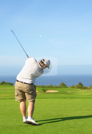Golfer on the fairway stock photo, Young male golfer hitting the ball from the fairway next to the ocean on a beautiful summer day by Elena Weber (nee Talberg)
