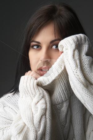 Portrait of beautiful brunette woman stock photo, Portrait of a beautiful young brunette woman wearing a white oversized jersey on black background by Elena Weber (nee Talberg)