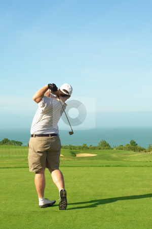 Golfer on the green stock photo, Young male golfer hitting the ball from the green on a beautiful summer day by Elena Weber (nee Talberg)