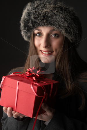 Portrait of beautiful brunette woman stock photo, Portrait of a beautiful young brunette woman wearing a winter jacket and fur hat holding red gift box on black background by Elena Weber (nee Talberg)