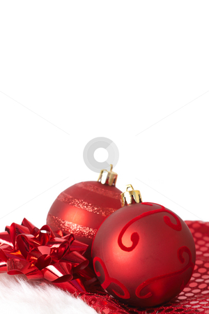 Red Christmas baubles on Santa hat stock photo, Two red Christmas baubles on Santa's hat with red bow isolated on white background with copy space. Shallow depth of field by Elena Weber (nee Talberg)