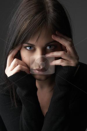 Portrait of beautiful brunette woman stock photo, Portrait of a beautiful young brunette woman with blue eyes wearing a black jersey on dark background by Elena Weber (nee Talberg)