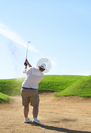 Golfer in the sand bunker stock photo, Young male golfer hitting the ball from the sand bunker on a beautiful summer day by Elena Weber (nee Talberg)