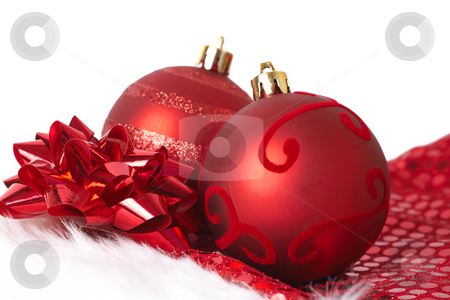 Red Christmas baubles on Santa hat stock photo, Two red Christmas baubles with a bow on Santa's hat isolated on white background with copy space. Shallow depth of field by Elena Weber (nee Talberg)