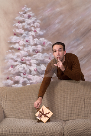 Secret Santa stock photo, A secret santa is leaving behind his gift on a sofa and telling the viewer to be quiet by Richard Nelson