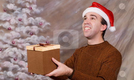 Gift Offer  stock photo, A young man wearing a Santa hat is holding and offering a gift to someone the viewer can't see by Richard Nelson