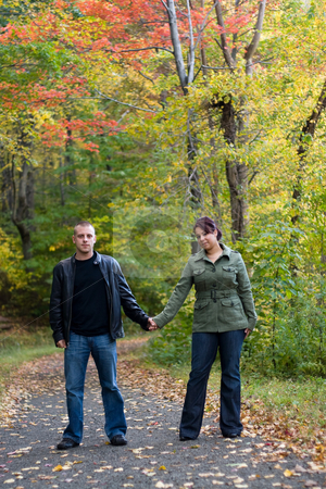 Young Couple In Love stock photo, A young happy couple on a path in the woods during Autumn. by Todd Arena