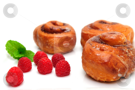 Raspberry and Cinnamon Rolls stock photo, Glazed cinnamon roll and fresh raspberries with a sprig of mint leaves isolated on white by Lynn Bendickson
