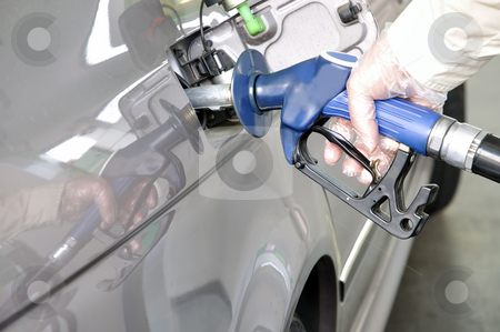 At the petrol station. stock photo, Close-up of a man's hand using a petrol pump to fill his car up with fuel. by Liana Bukhtyyarova