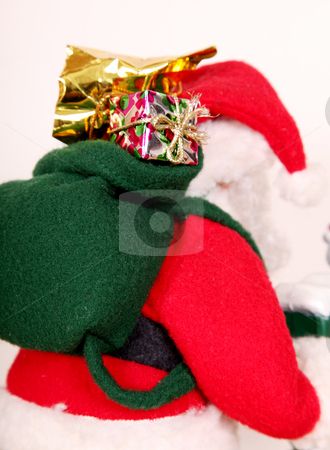 Christmas stock photo, Santa on his back carrying Christmas presents by Giuseppe Ramos