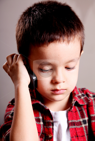 Child stock photo, Child talking on mobile phone, looking down by Giuseppe Ramos