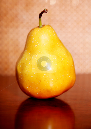 Pear stock photo, Articial yellow pear on a wooden surface by Giuseppe Ramos