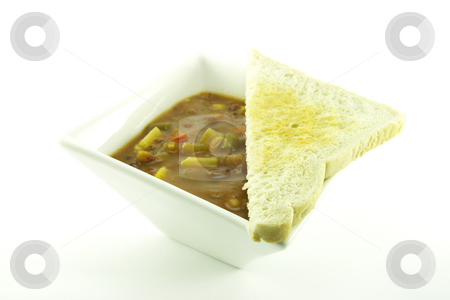 Soup in a White Bowl stock photo, Hot chunky vegetable soup in a small square white bowl with toast on a white background by Keith Wilson