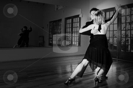 Two ballroom dancers practicing in their studio stock photo, A young adult couple dancing and practicing ballroom dancing together in a studio - Focus on man, black and white image by Sean Nel