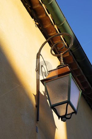 Streetlight on the building stock photo, Streetlight against a building in Antibes, France. by Sean Nel