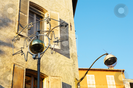 Buildings in Antibes stock photo, Building with shutters on windows and street lamp in Antibes, France. by Sean Nel