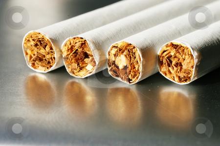Tobacco #1 stock photo, Four cigarettes on a cigarette case by Sean Nel