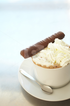 Cappuccino in coffee cup stock photo, Fresh foamy cappuccino in white coffee cup on a silver background with a chocolate biscuit ? Shallow Depth of Field, focus on Foam at front of cup by Sean Nel