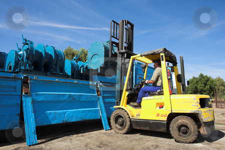 Forklift #1 stock photo, Yellow Forklift placing cargo on Flatbed truck for dispatch by Sean Nel