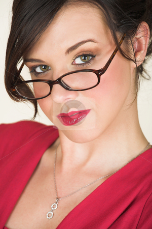 Young caucasian businesswoman stock photo, Young adult brunette businesswoman with horn rimmed glasses and a red dress. She is Caucasian and wears bright red lipstick. by Sean Nel