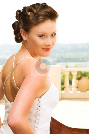 Sexy young brunette bride wearing white wedding gown stock photo, Young beautiful brunette bride with champagne colored wedding gown and red lips. She is looking over her shoulder with an alluring and seductive look in her green eyes. She is outdoors on a sunny day by Sean Nel