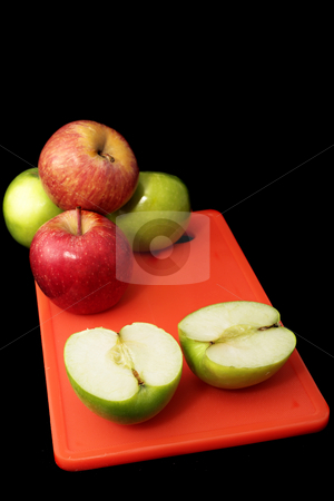 Apple #7 stock photo, Red and green apples on red plastic cutting board - black background by Sean Nel