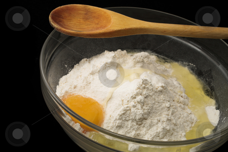 Baking #1 stock photo, Flour & egg in a glass bowl with wooden spoon, black background by Sean Nel