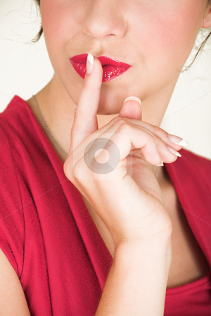 Young caucasian businesswoman stock photo, Young adult brunette businesswoman with her finger in front of her lips and wearing a red dress. She is Caucasian and wears bright red lipstick. White background, not Isolated - Shallow Depth of Field by Sean Nel