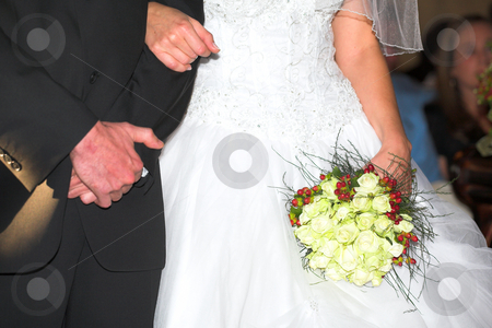 Wedding bouquet and bridal couple stock photo, Bride and groom during the wedding ceremony and the bride is holding a white rose and berry wedding bouquet - Shallow depth of field - Focus on the flowers by Sean Nel