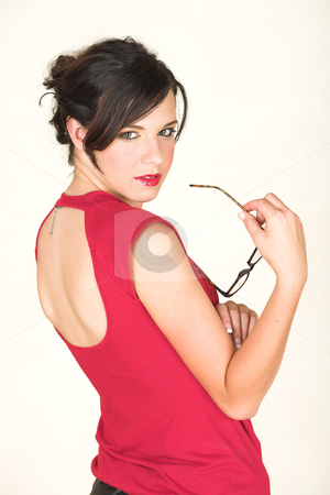 Young caucasian businesswoman stock photo, Young adult brunette businesswoman with horn rimmed glasses and a red dress. She is Caucasian and wears bright red lipstick and cheekily looking over her shoulder. White background, not Isolated by Sean Nel
