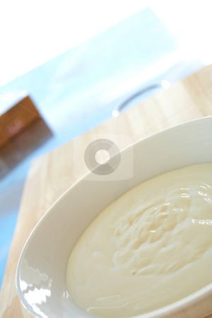 Breakfast yogurt stock photo, Fresh thick dairy yogurt for breakfast in a white bowl on a kitchen table by Sean Nel