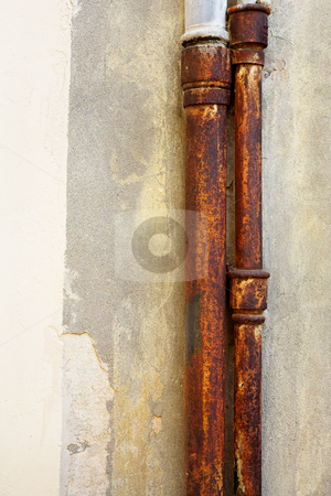 Rusted pipes on the wall stock photo, Rusted pipes against a brown wall. Copy space by Sean Nel