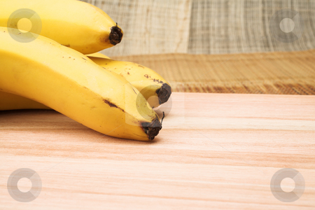 Banana #1 stock photo, Three bananas on a wooden cutting board - copy space by Sean Nel