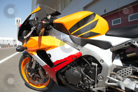 Side of a superbike stock photo, Orange superbike next to the racetrack by Sean Nel