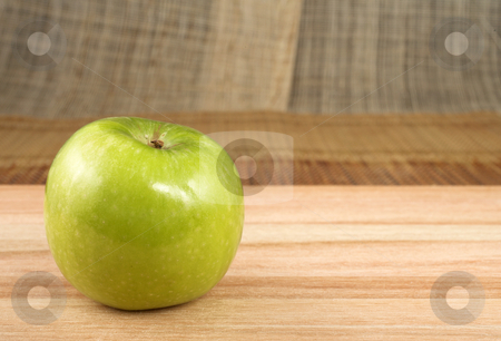 Apple #3 stock photo, Green apple on wooden cutting board - copy space by Sean Nel