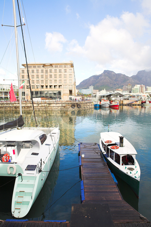 Boats in the Cape Town Waterfront harbor stock photo, Two tourist boats in the Cape Town waterfront harbor with three boats reflecting in the water in the background and part of the city skyline visible by Sean Nel