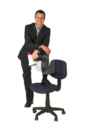 Businessman #257 stock photo, Businessman wearing a suit and a grey shirt.  Making a stunt on an office chair with a megaphone in his hand. by Sean Nel